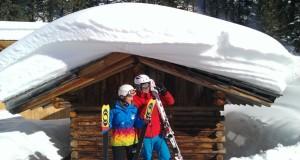 Zwei Skifahrer stehen vor einer tief verschneiten Holzhütte (Skigebiet Hochzeiger)